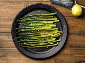 Roasted asparagus on a plate with lemon zest.