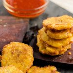Crispy fried plantains (or banan peze) stacked on a plantain press with sauce in the background.
