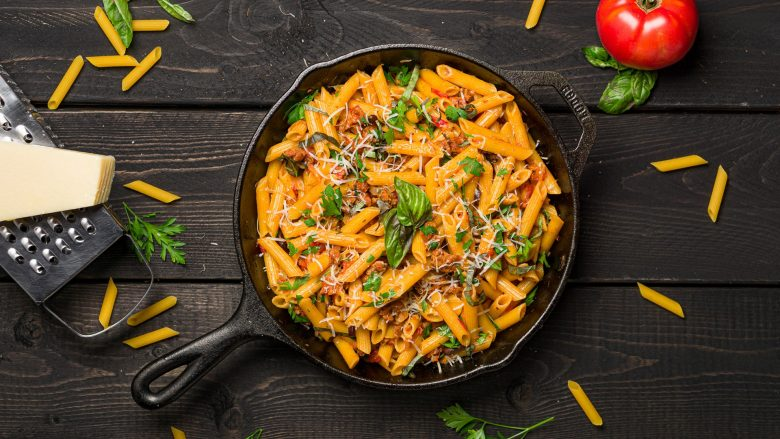 Penne pasta in a cast iron pan viewed from above.